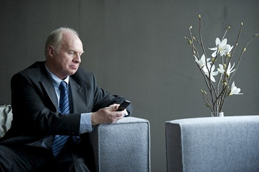 Senior businessman sitting on sofa and using cell phone_